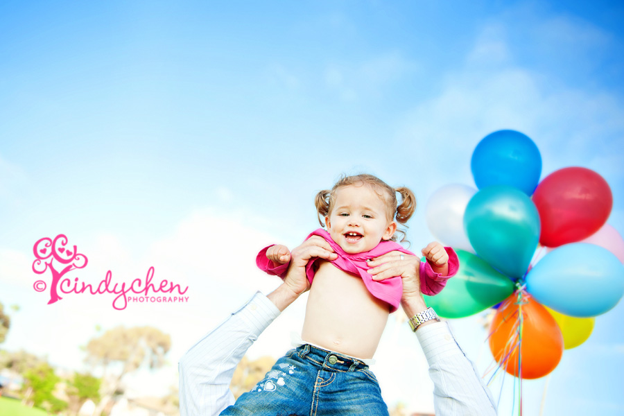 little girl up in the blue sky with balloons