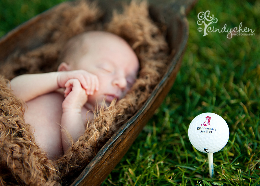 Sleeping newborn baby with golf ball on the green
